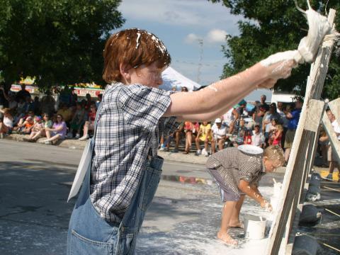Whitewashing the fence during National Tom Sawyer Days