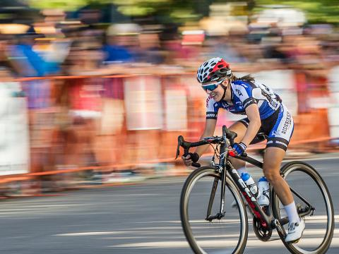 Crowds cheering from the sidelines as cyclists race at the Twilight Criterium