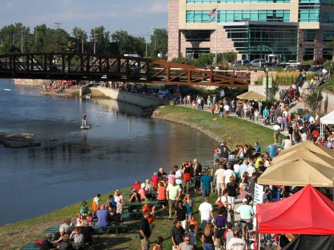 Strolling among displays and food booths at the Downtown River Greenway