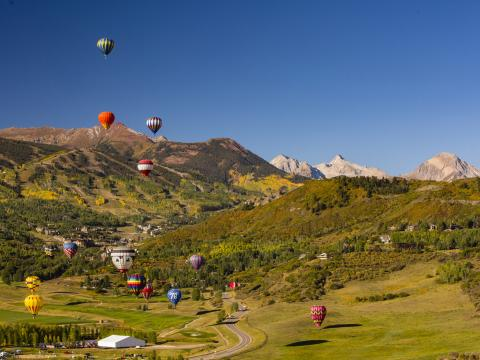 Hot air balloons floating over the landscape during the Snowmass Balloon Festival in Colorado